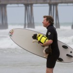 Man Carrying Dog Surf